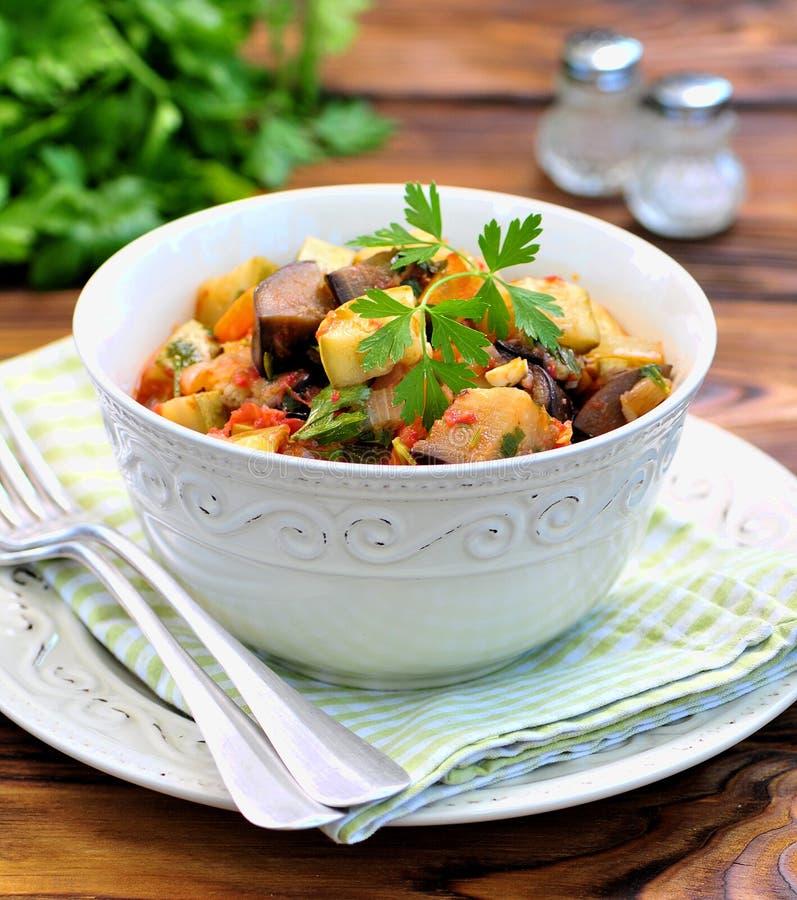 Plantaardige hutspot van aubergine, courgette, uien, wortelen, tomaten, knoflook en peterselie stock foto's