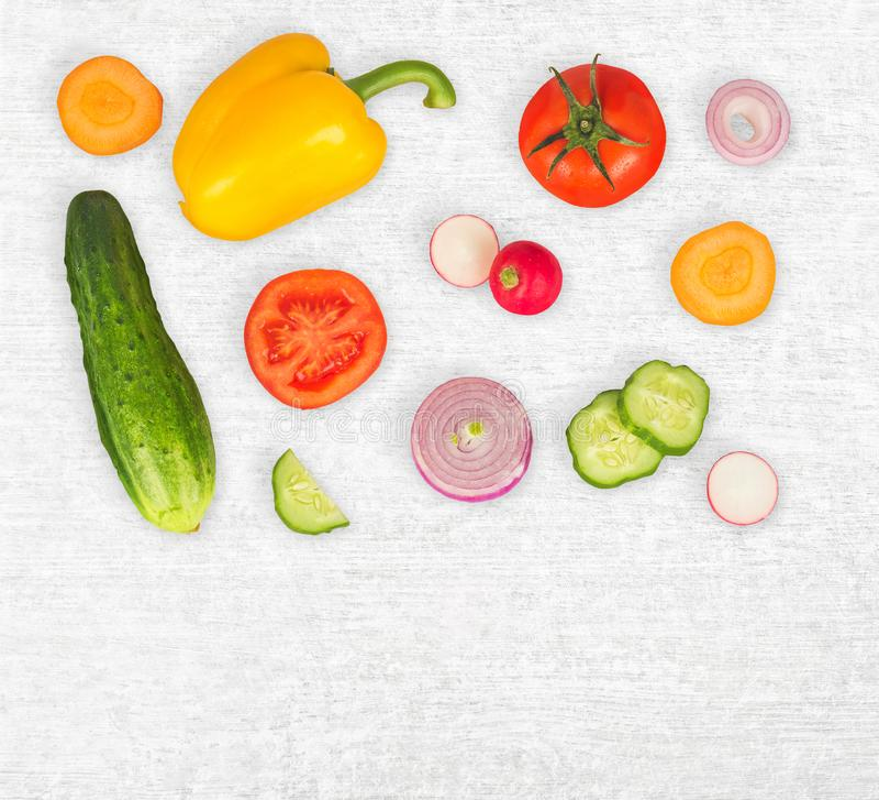Plantaardige mengeling op witte houten geïsoleerde achtergrond Verse gele peper, gehakte tomaten, ui, komkommerplak, wortel, radi stock fotografie