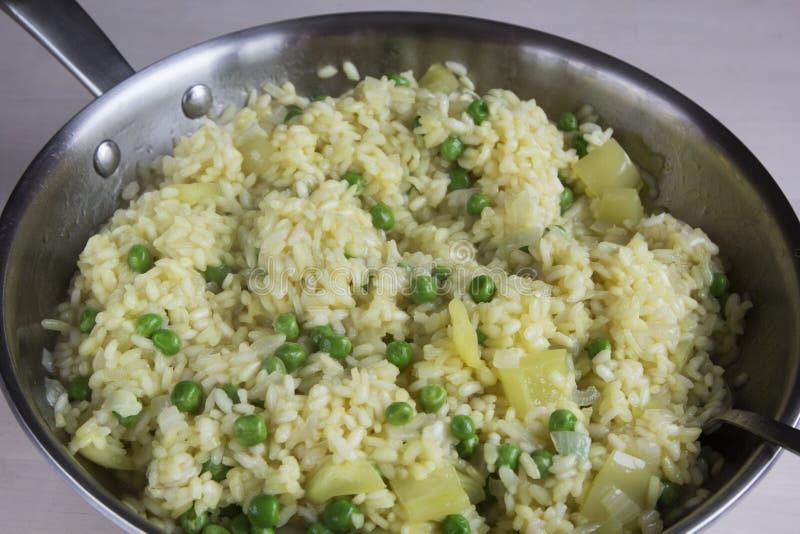 Plantaardige risotto met saffraan en groene erwten stock foto's