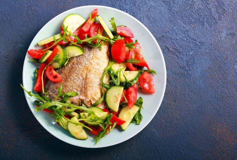 Plantaardige salade en gebraden doradovissen stock afbeelding