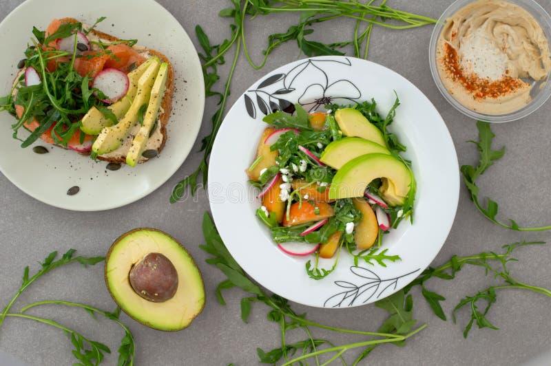 Plantaardige salade met avocado, arugula, radijs, perzik en sandwich whith humus Dieet gezond voedsel Houten achtergrond stock foto