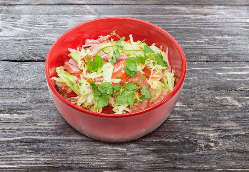 Plantaardige salade met ham in de rode saladekom royalty-vrije stock afbeeldingen