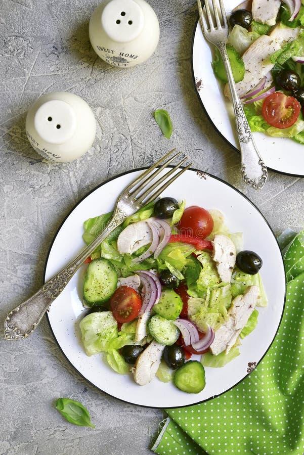 Plantaardige salade met kip en zwarte olijven op een witte plaat royalty-vrije stock afbeelding