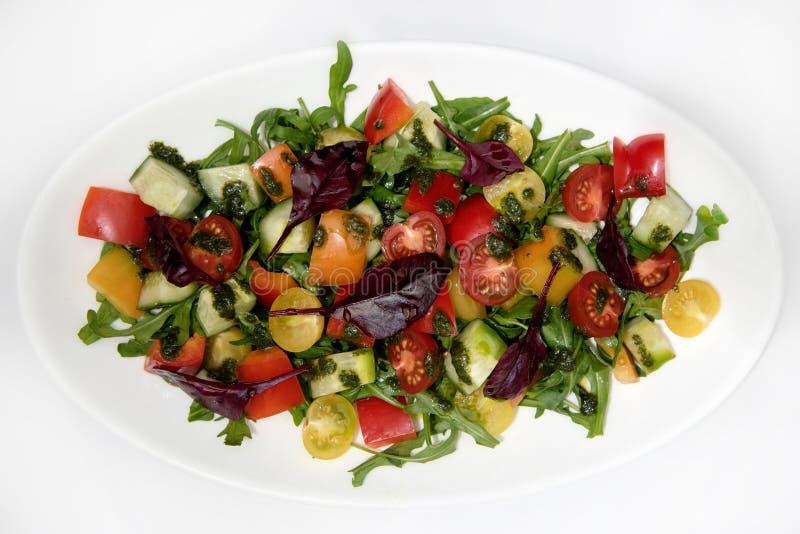 Plantaardige salade met tomaten, komkommers, groene paprika, arugula en olijfolie stock afbeelding