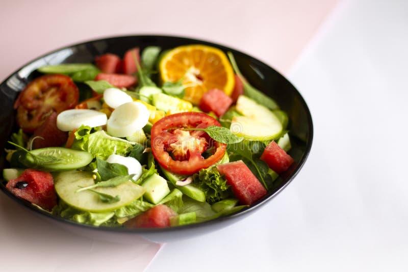 Plantaardige salade op een zwart van het het verliesconcept van het plaatgewicht Gezond voedsel stock afbeelding