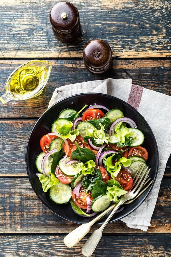Plantaardige salade van verse tomaat, komkommer, spinazie, ui en sla op plaat royalty-vrije stock foto