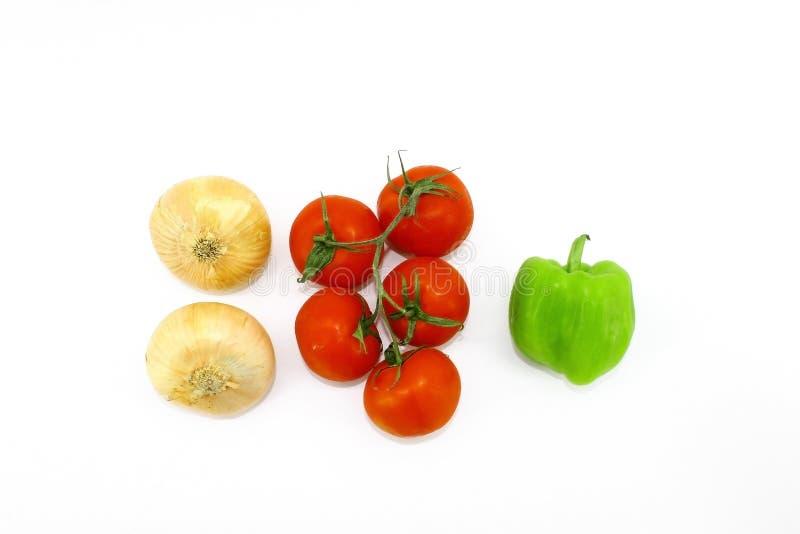 Plantaardige samenstelling op een witte achtergrond - uien, tomatenrood op een tak en groene paprika royalty-vrije stock afbeeldingen