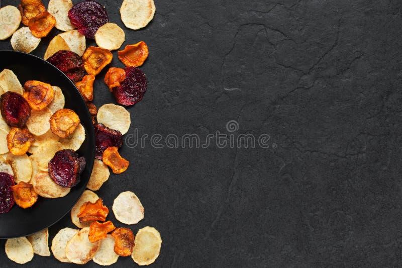 Plantaardige spaanders op de zwarte plaat stock afbeelding
