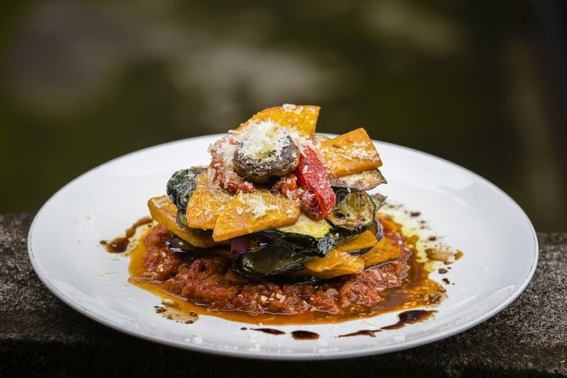 Plantaardige stapel - pompoen, courgette, rood die capsicum, aubergine en paddestoel in een tomaat, een ui, en een knoflooksaus w royalty-vrije stock afbeeldingen