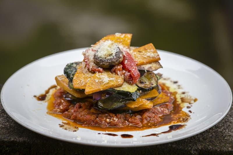 Plantaardige stapel - pompoen, courgette, rood die capsicum, aubergine en paddestoel in een tomaat, een ui, en een knoflooksaus w stock afbeelding