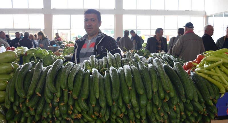 Plantaardige verkoper in markt stock foto