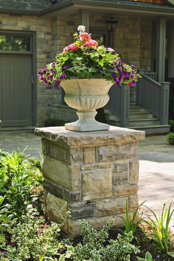 Plantador de piedra delante de la casa imagenes de archivo