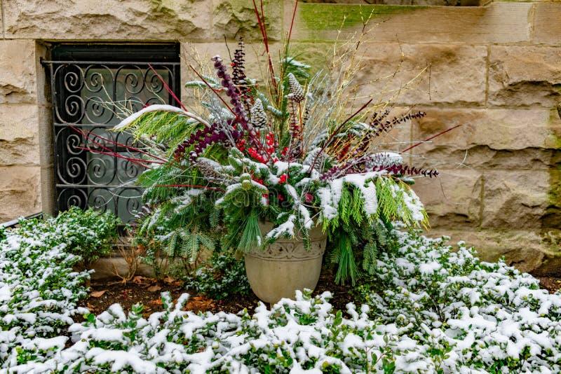 Plantador del día de fiesta con las ramas del pino fuera de un hogar en un jardín cubierto con nieve durante invierno imagen de archivo