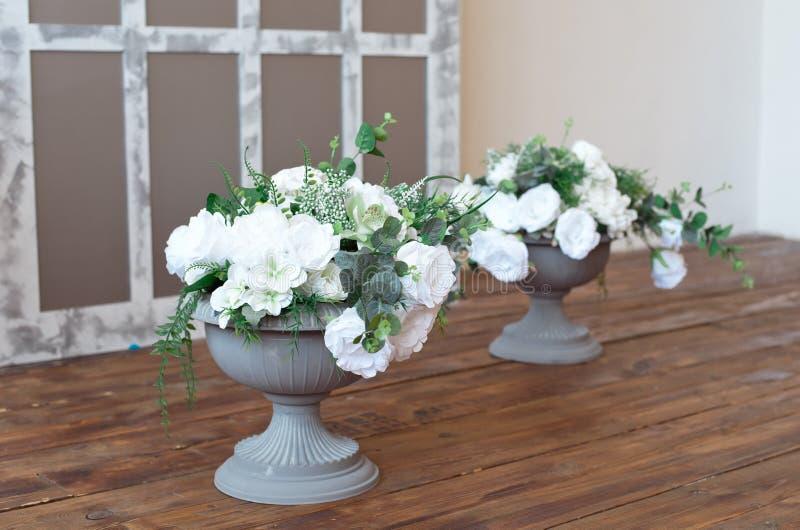 Plantador italiano branco antigo da urna com as flores na sala barroco branca do estilo foto de stock