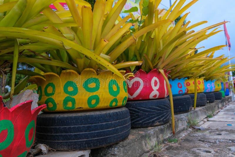 Plantadores verdes coloridos feitos dos pneus reciclados fotos de stock