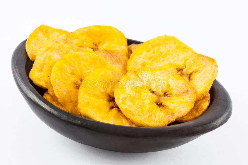 Plantain fried coins in a traditional black clay bowl royalty free stock photos