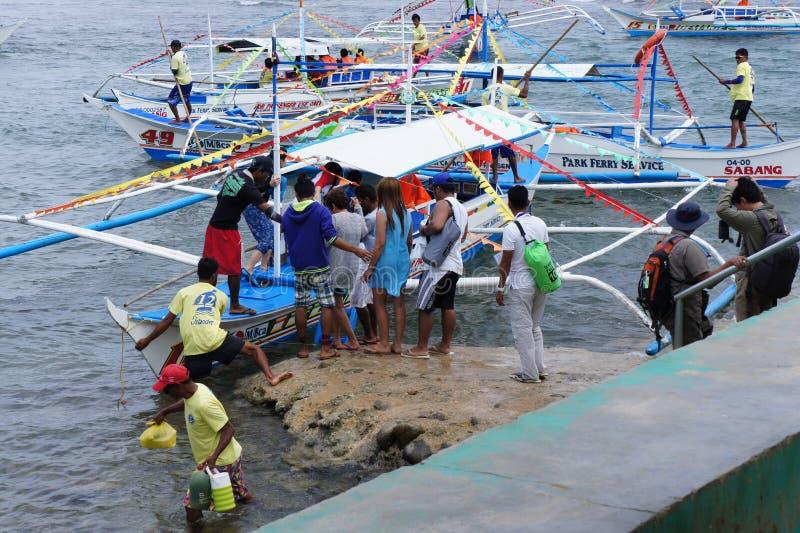Plantando os grupos de turistas no barco, indo em uma excursão ao rio subterrâneo Puerto Princesa fotos de stock