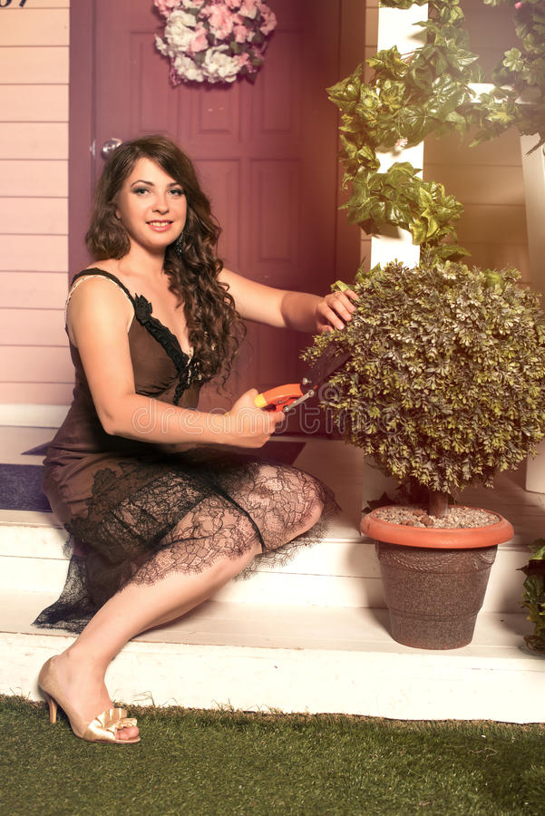 Plantas de corte morenos da mulher com os secateurs no jardim imagens de stock