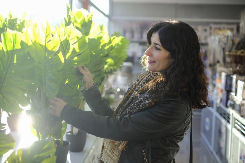 Plantas de la compra de la mujer en el invernadero, seleccionando los potes imágenes de archivo libres de regalías