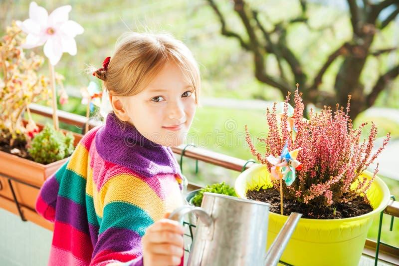 Plantas de riego de la niña en el balcón fotos de archivo
