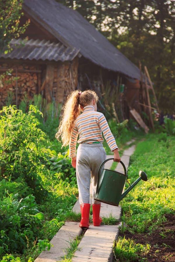 Plantas de riego lindas de la niña con la regadera en jardín C imagenes de archivo