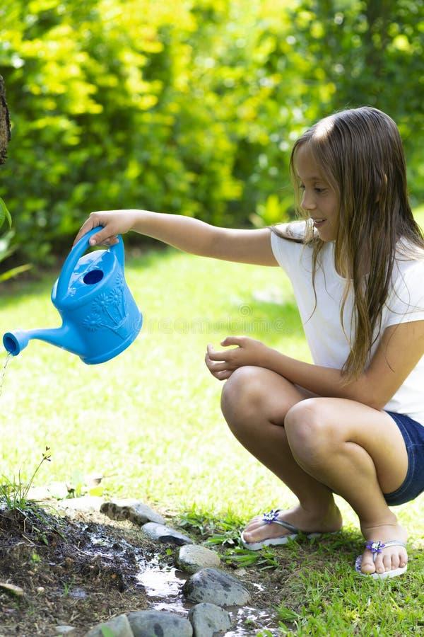 Plantas molhando da menina feliz foto de stock royalty free