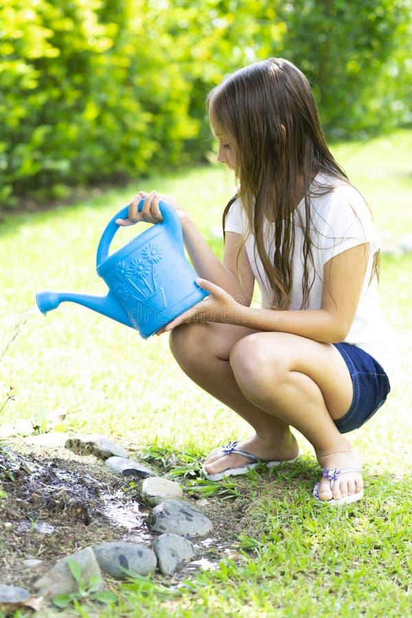 Plantas molhando da menina feliz imagens de stock royalty free