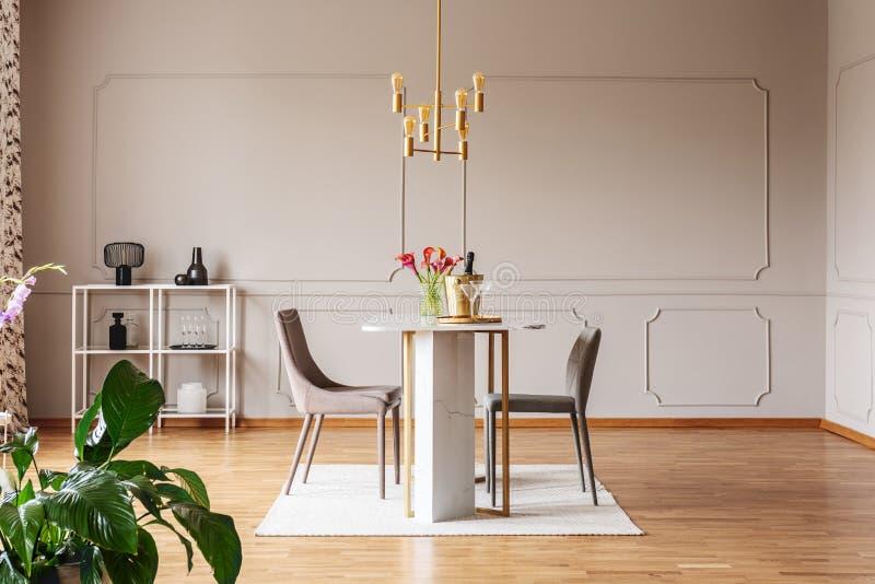 Plante perto das cadeiras na tabela com as flores no interior cinzento moderno da sala de jantar com lâmpada do ouro Foto real foto de stock