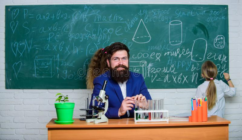 Plantera fröt för morgondag Allmänhet- eller privatskolalärare Kemilärare med mikroskopet och provrör på royaltyfri fotografi