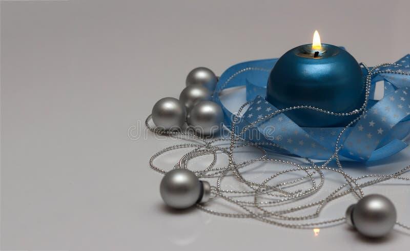 Plantilla de la tarjeta de felicitación hecha de vela azul con la cinta azul, las bolas de plata de la Navidad y la cadena de got imágenes de archivo libres de regalías