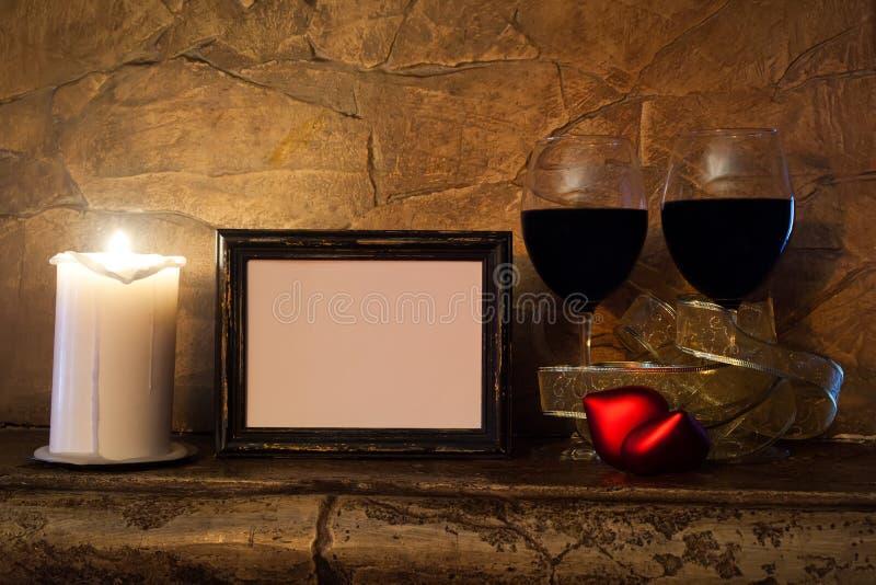 Plantilla del día de tarjetas del día de San Valentín vidrios con el vino, la vela, el corazón del peluche y el marco rojos de la imagen de archivo