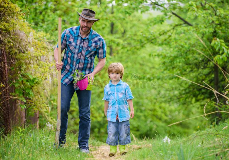 Planting flowers. Dad teaching little son care plants. Little helper in garden. Make planet greener. Growing plants. Take care of plants. Day of earth. Boy and royalty free stock image