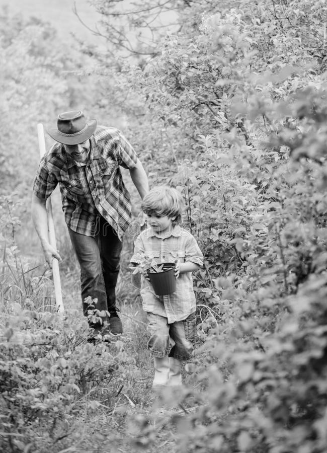 Planting flowers. Growing plants. Boy and father in nature with watering can and shovel. Dad teaching son care plants. Arbor day. Planting trees. Tree planting stock photos