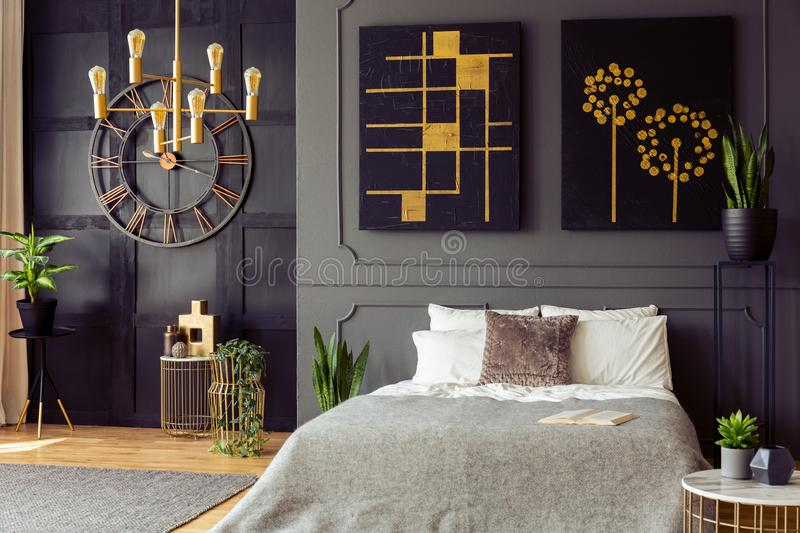 Plants and black and gold posters in grey bedroom interior with clock and bed with pillows. Real photo royalty free stock photos