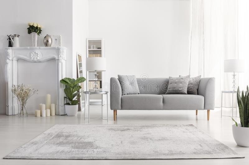 Plants and carpet in white living room interior with candles next to grey couch. Real photo. Plants and carpet in white living room interior with candles next to stock images