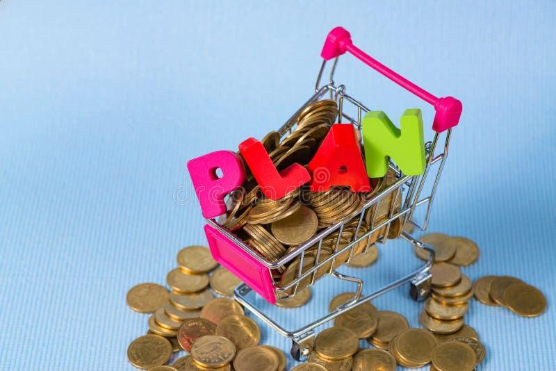 PLANUJE drewnianego tekst i sterty monety z wózek na zakupy lub super fotografia royalty free