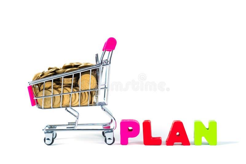 PLANUJE drewnianego tekst i sterty monety z wózek na zakupy lub super fotografia stock