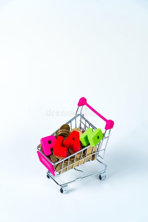 PLANUJE drewnianego tekst i sterty monety z wózek na zakupy lub super obraz stock
