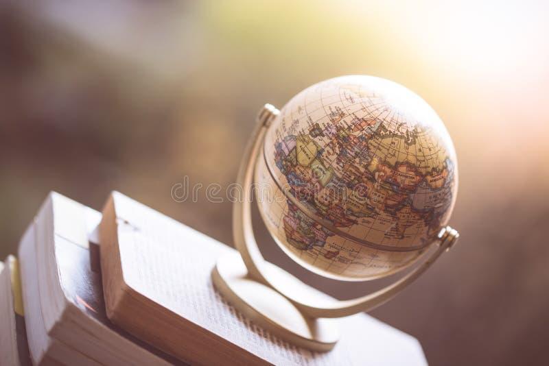 Planung der folgenden Reise: Miniaturkugel auf einem Stapel Büchern lizenzfreie stockfotos