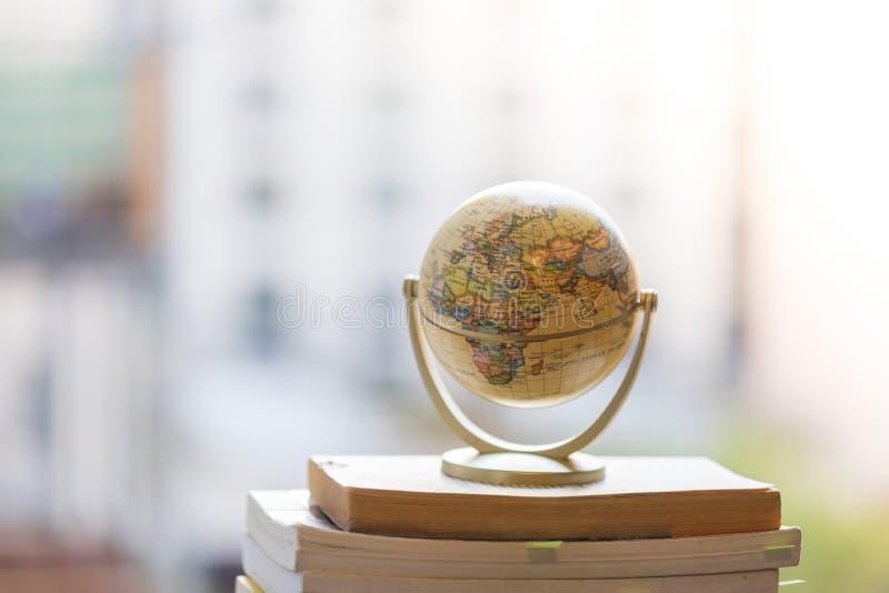 Planung der folgenden Reise: Miniaturkugel auf einem Stapel Büchern lizenzfreie stockfotografie