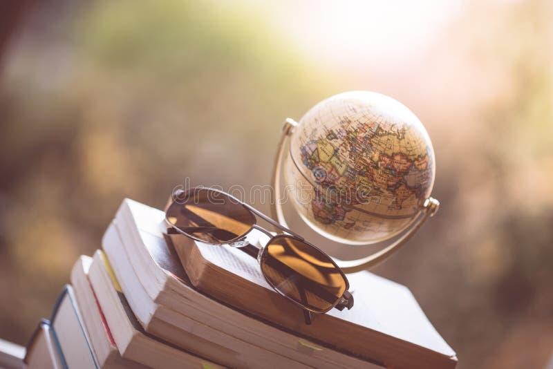 Planung der folgenden Reise: Miniaturkugel und Sonnenbrille auf einem Stapel Büchern lizenzfreie stockfotografie