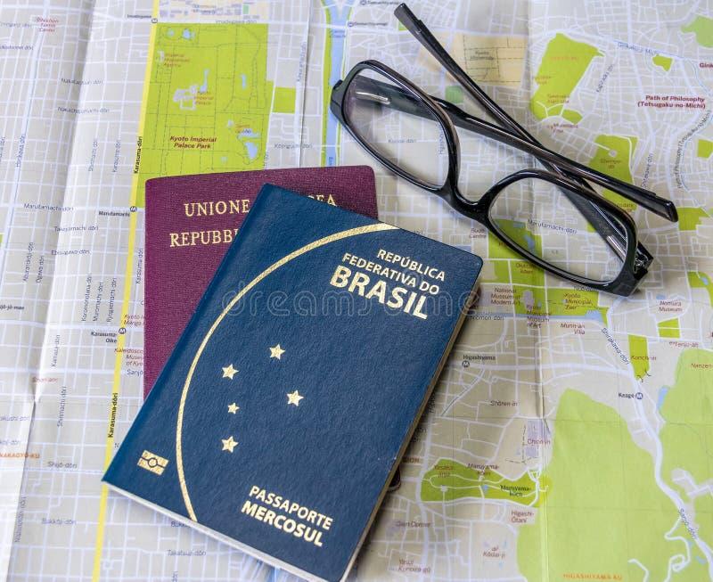 Planung die brasilianischen und italienischen Pässe einer Reise - auf Stadtplan mit Gläsern stockfotografie