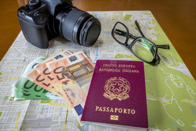 Planung die italienischen und brasilianischen Pässe einer Reise - auf Stadtplan mit Euro berechnet Geld, Kamera und Gläser stockfotografie