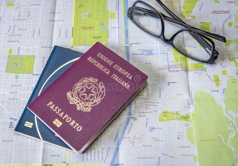 Planung die italienischen und brasilianischen Pässe einer Reise - auf Stadtplan mit Gläsern lizenzfreies stockbild