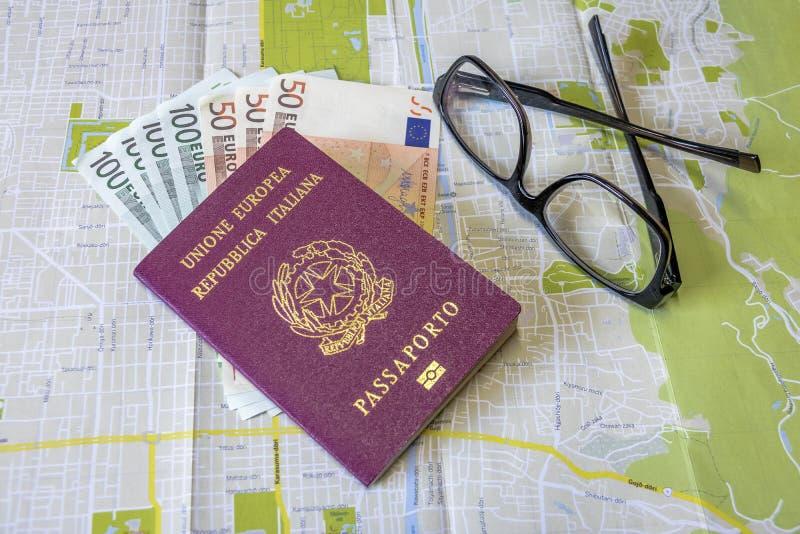 Planung eine Reise - italienischer Pass auf Stadtplan mit Euro berechnet Geld und Gläser lizenzfreie stockfotografie