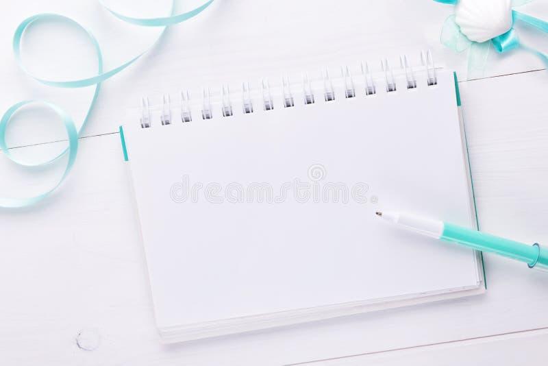 Planungsstillleben der Modefrau, Gegenst?nde auf Wei?: emply notepade und Stift und gem?tliches tadelloses Band stockbilder