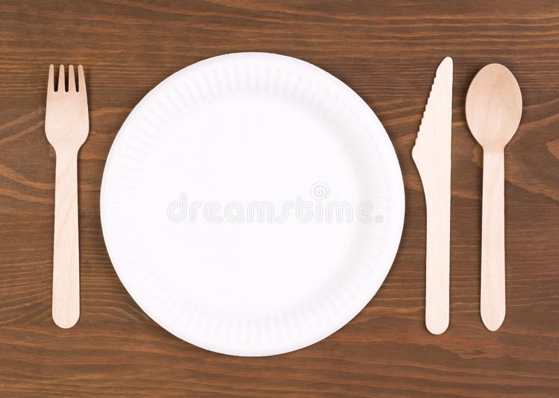 Plaque à papier jetable et couverts en bois sur la table en bois photos libres de droits