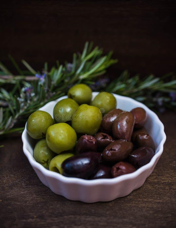 Plaque avec olives vertes et noires et romarin images stock