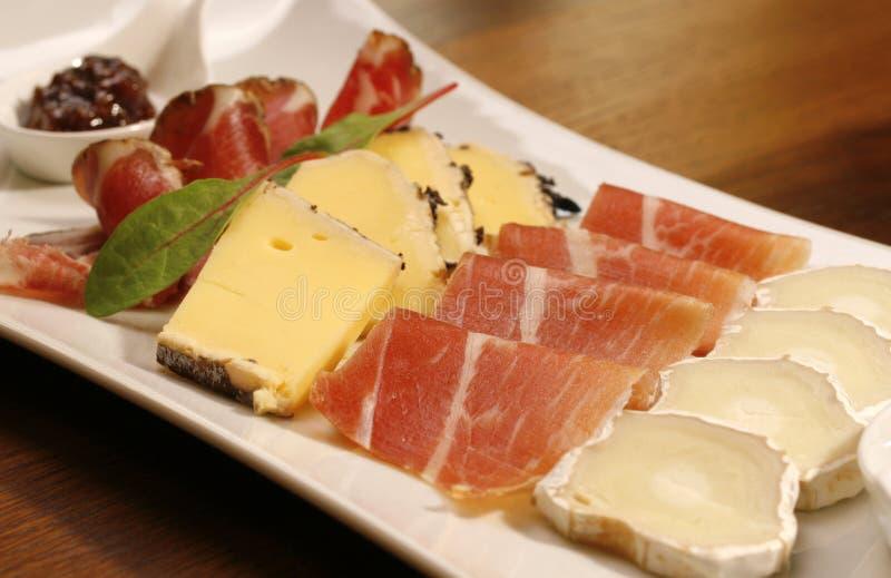 Plaque d'hors-d'oeuvres (fromage et jambon) sur la table en bois brune images stock