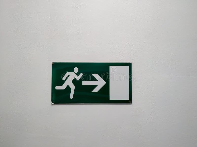 Plaque d'indication de sortie verte avec une figure de l'homme et une flèche vers la porte comme instruction d'orientation en cas photographie stock libre de droits